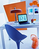 Designer swivel chair in front of retro table lamp on glass desk and coloured panel