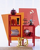 Magazines, cushions and various ornaments in stacked, red shelving modules in front of brightly coloured partitions