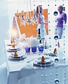 Festive table set with sparklers for New Year and party guests in background
