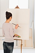 Woman standing in front of blank canvas on easel in artist's studio