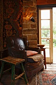 Old leather armchair in corner of room next to French windows in simple country house