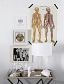 Various drawings and photos on wall above small table holding lamp, laboratory glassware and china objects