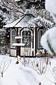 Summerhouse and birdbath in snowy garden