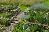 Flowering cottage garden with rough stone walls and cobbled path