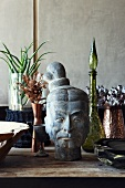 Oriental stone head and vases made from various materials on wooden table