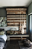 Teardrop-shaped pendant lamps in front of upcycled wood wall element in bedroom