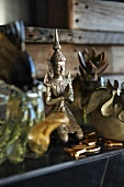 Bronze statue of a kneeling Buddha on table