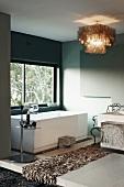 Designer-Badezimmer - Flokatiartiger Läufer auf weißem Fliesenboden vor Badewanne am Fenster und Deckenleuchte aus hellbraunen Perlmuttplättchen