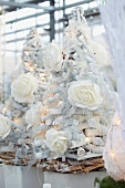 Christmas trees made from white twigs with white roses and fairy lights