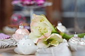 Christmas table centrepiece of white amaryllis and baubles on set table