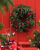 Advent wreath with red felt stars hanging on red wooden wall and cake stand holding baubles and apples on terrace