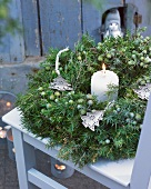 Winter wreath of juniper with Christmas-tree-shaped decorations and candle on terrace