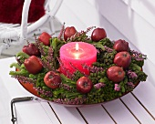 Winter wreath of brunia and heather with apples and candle