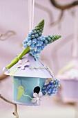 Blaues Vogelhäuschen mit Traubenhyazinthen als Frühlingsdeko