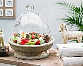 Tulips and tulip bulbs in stone bowl under glass cloche