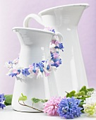 White pitcher decorated with garland of hyacinth florets