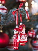 Little boy and girl Christmas tree baubles hung from branch with red ribbon