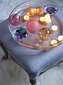Kugeln und brennende Teelichter in Glasschale auf gepolstertem Schemel im Rokokostil