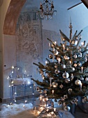 Dekorierter Weihnachtsbaum mit brennenden Kerzen vor modernem Stuhl aus transparentem Kunststoff mit Engeln dekoriert