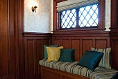Cushions on wooden bench built into wooden wall panelling below window