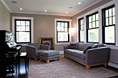 Sofa, armchair and ottoman upholstered in grey in music room with traditional atmosphere