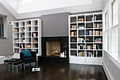 Elegant interior with fireplace flanked by white shelving contrasting with grey walls and dark wood floor