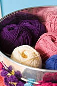 Balls of wool of different colours in tin