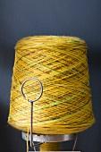 Bobbin of yellow yarn against blue background