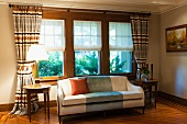 Pale sofa and round side tables in front of window with half-opened blinds and gathered curtains in traditional living room