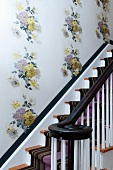 Traditional staircase with striped runner and floral wallpaper