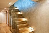 Glastrennscheibe vor moderner Treppe mit Einbauleuchten in Wand eines minimalistischen Treppenhauses