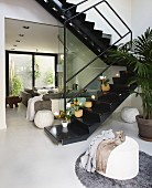 Black, lacquer zig zag stairs in an open living room with upholstered furniture in bright, gray fabric