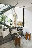 Gray, designer sofa with decorative pillows and small tables on a Flokati rug with a glass wall separating it from the open living room staircase