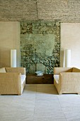 Pair of armchairs in front of unrendered section of old, rough stone wall as accent in renovated, Majorcan farmhouse