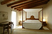 Natural materials and colours in Majorcan bedroom with canopied bed and small writing desk