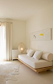 Modern painting above simple sofa structure with thick seat mattress and bolster cushions in minimalist interior