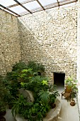 Foliage plants and wooden chair surrounded by tall stone walls in glass-roofed courtyard