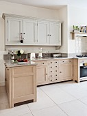 Bright, l-shaped kitchen in Shaker style with base cabinets accessible from both sides