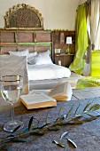 Olive twig and glass on table in front of double bed with white bed linen in simple bedroom