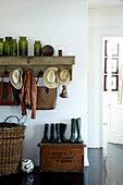 Vintage mudroom with Wellington boots on an old wooden chest and collection of bottles on a wall coat rack
