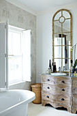 Bathroom with latticed mirror on shabby-chic chest of drawers with curved front next to free-standing, retro bathtub
