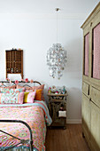 Fresh, country-house bedroom with display case, chandelier of stars, floral bed linen on iron bed and rustic wooden wardrobe