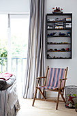 Garden deckchair below toys on wall-mounted shelves and foot of bed in front of French windows