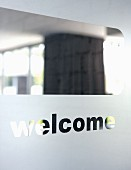 View through the clear glass of a frosted glass entrance door with 'welcome' engraved in it