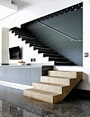 Plywood step element at end of sideboard combined with terrazzo floor and stone treads on interior staircase