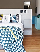 Bed linen with geometric patterns on double bed against partition headboard