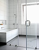 Bathroom with white tiles and grey plastic flooring separated by glass wall