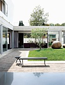 Courtyard of low house with corner bench on terrace running around central lawn with large boulders