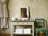 Badezimmer mit Waschtisch im Hotel im Jugendstil mit Spiegel, Waschutensilien, Blume, Handtüchern, Bademantel und Stuhl