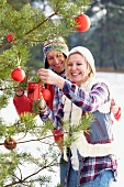 Couple decorating Christmas tree in woodland